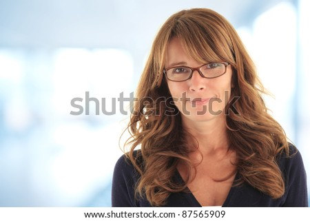 Attractive blond mature business woman in her office with copy space (blue, de-focused background) - stock photo