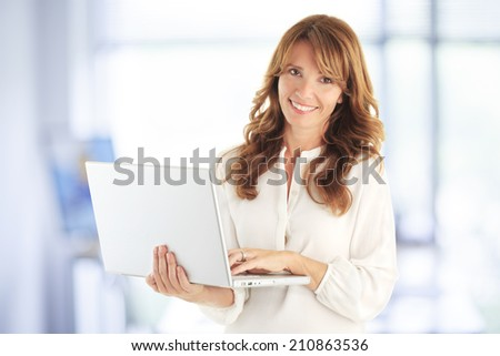 Attractive blond mature business woman with laptop against white background with copy space - stock photo
