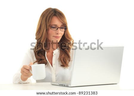 Attractive blond mature business woman working on her laptop and drinking coffee ( against white background with copy space )