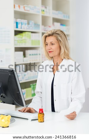 Attractive blond middle-aged female pharmacist checking stock on her computer as she stands at the counter in the pharmacy - stock photo
