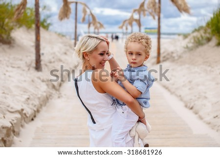 Attractive blond moter holding her child over road to the beach. - stock photo