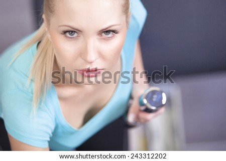 Attractive blond sporty girl doing triceps training with a dumbbell  - stock photo