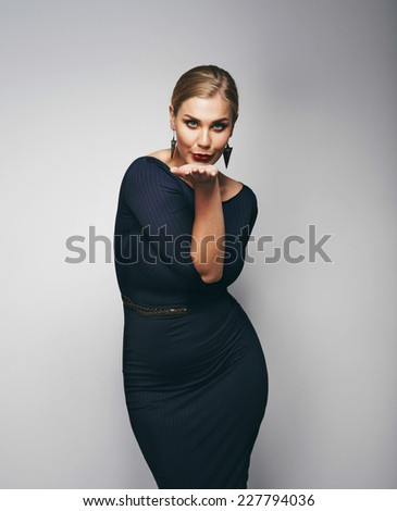 Attractive blond woman blowing kiss at camera against grey background. Curvy young female model in dress. - stock photo