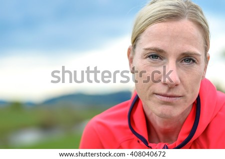 Attractive blond woman dressed in bright pink sportswear bending forwards and looking intently at the camera with a quiet smile - stock photo