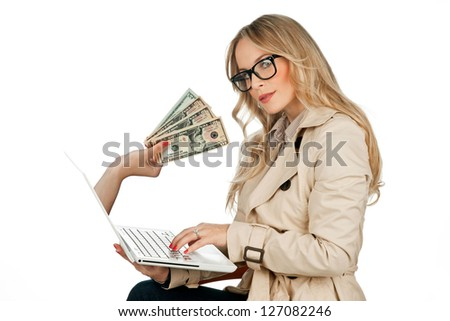 attractive blond woman holding laptop with hand coming out of the screen with money - stock photo