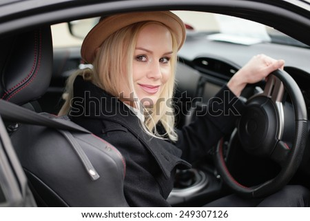 Attractive blond woman in a trendy hat at the wheel of her car turning to smile at the came ram view through the side window - stock photo