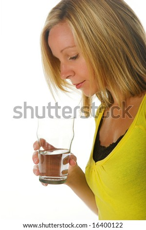 Attractive blond woman looking into a glass of water. Portion of photographers commission of this image will be donated to Autism Ontario.
