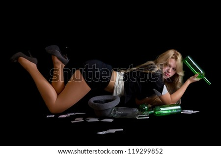 Attractive blond woman lying on floor holding empty bottle of wine and playing cards - stock photo