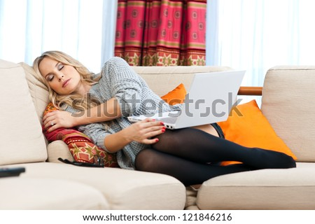 attractive blond woman napping on the sofa after work on her laptop - stock photo