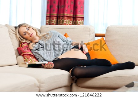 attractive blond woman slept on the sofa while reading book - stock photo