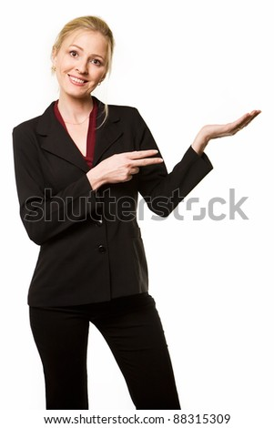 Attractive blond woman wearing a black business suit smiling holding up one hand and pointing at the empty hand with the other hand - stock photo