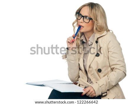 attractive blond woman with notebook thinking - stock photo