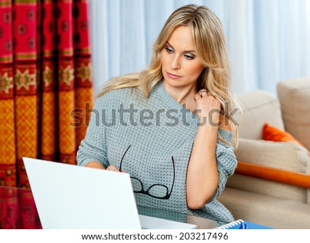 attractive blond woman writer sitting at the table and writing on the laptop computer - stock photo