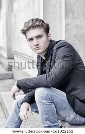 Attractive blond young man in jeans and jacket, sitting outdoors looking in camera - stock photo