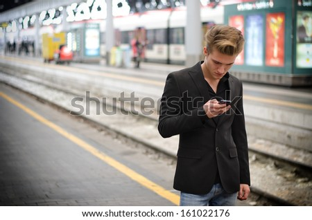 Attractive blond young man in train station using cellphone (mobile) - stock photo