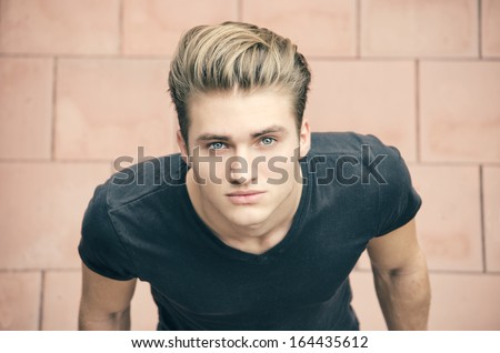 Attractive blond young man shot from above, looking up towards camera - stock photo