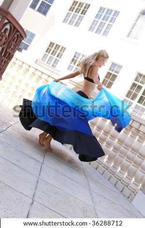 attractive blonde belly dancer spinning with veil outside on balcony - stock photo