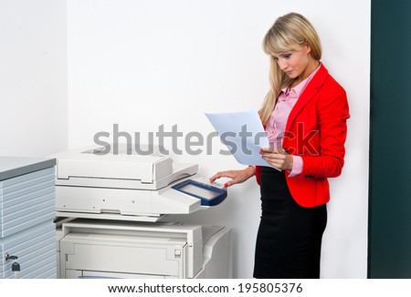 attractive blonde business woman with documents standing next to printer - stock photo