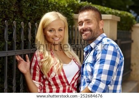 Attractive blonde casual woman and stubbly handsome man outdoor, leaning against fence, smiling, looking at camera. - stock photo
