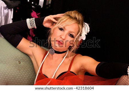 Attractive blonde dressed as madam or prostitute, could also be a sexy elf or mrs. claus for christmas, looking directly at viewer.  Shot with blue and red strobes. - stock photo