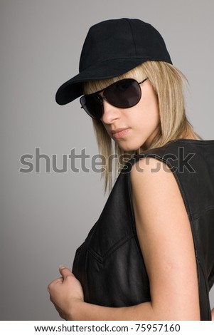Attractive blonde girl in a sunglasses and cap. - stock photo