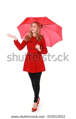 Attractive blonde girl wearing a red coat and holding an umbrella. standing, holding hand out to touch rainfall. isolated on white background. - stock photo