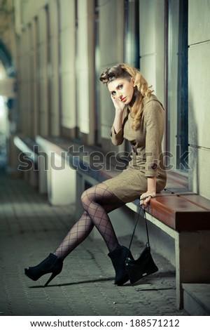 Attractive blonde girl wearing short dress and high heels - urban scene. Fashion model with long sexy legs sitting on bench thinking. Elegant woman wearing outfit with Russian influence posing relaxed - stock photo