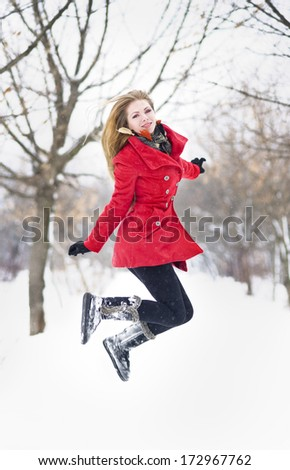 Attractive blonde girl with gloves, red coat and red hat posing winter snow.Beauty woman in the winter scenery.Young woman in wintertime outdoor - stock photo