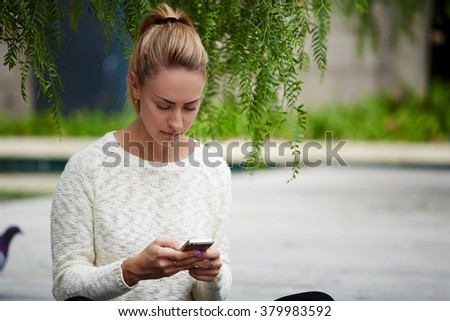 Attractive blonde hair woman chatting with mobile phone in social network while sitting alone in park, young female student reading text message on cell telephone while resting after strolling in city - stock photo