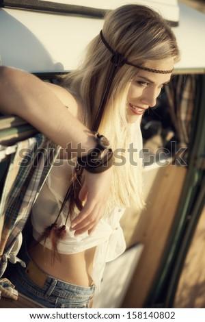 attractive blonde hippie girl beside an old caravan - stock photo