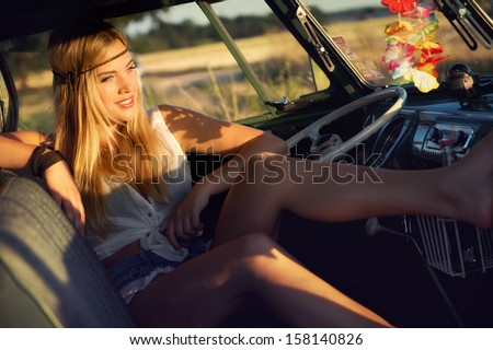 attractive blonde hippie girl in an old caravan - stock photo