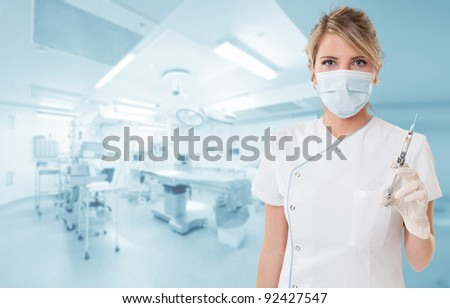 Attractive blonde holding a syringe in an operating room - stock photo