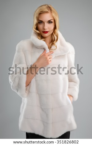 attractive blonde lady with red lips in white fur coat - stock photo