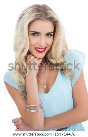 Attractive blonde model in blue dress looking at camera on white background