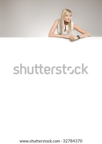 Attractive blonde over white empty board, lots of copyspace - stock photo