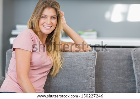Attractive blonde sitting on her couch smiling at camera in sitting room at home - stock photo