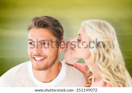 Attractive blonde whispering secret to boyfriend against wooden planks background - stock photo