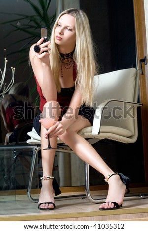 Attractive blonde with a glass of cocktail sending sms - stock photo