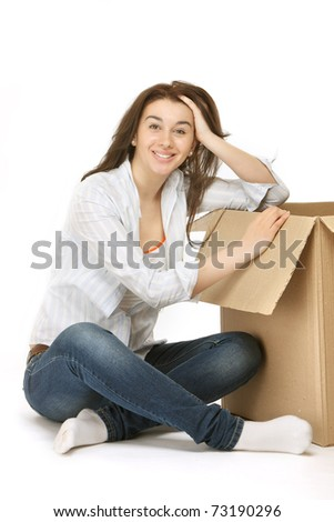 Attractive blonde woman lifting moving box - stock photo
