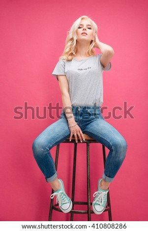 Attractive blonde woman posing on the chair over pink background - stock photo