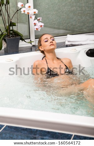 attractive blonde woman relaxing in jacuzzi whirlpool spa wellness healthcare - stock photo