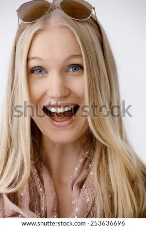 Attractive blonde woman shouting, laughing happy, looking at camera. - stock photo