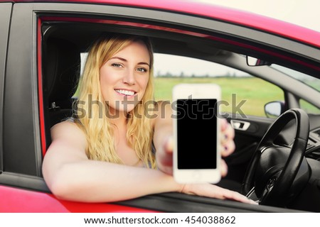 Attractive blonde woman showing smartphone out the window of a car. - stock photo