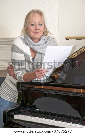 Attractive blonde woman singing while leaning on a black grand piano.