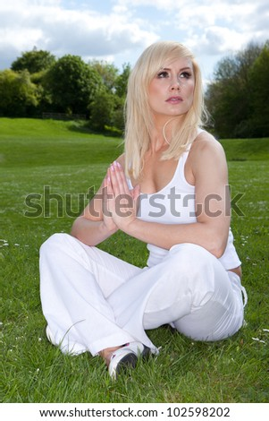 Attractive blonde woman sitting cross-legged on green grass meditating and looking to heaven - stock photo