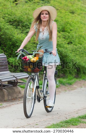 Attractive blonde woman with straw hat riding a bike with basket full of groceries. - stock photo