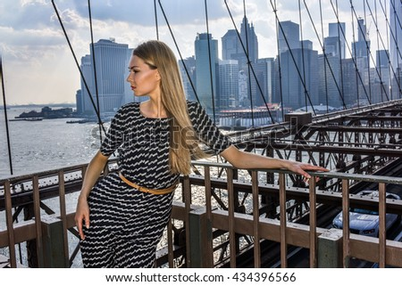 Attractive blonde young woman posing on the Brooklyn Bridge with city view on the background. - stock photo