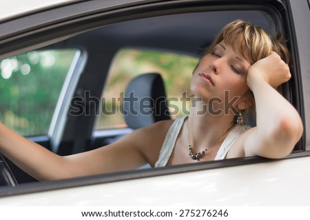 Attractive blonde young woman sleeping in a car stuck in traffic in a sunny day - stock photo