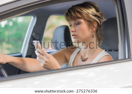 Attractive blonde young woman using mobile phone while driving a car, distracted - stock photo