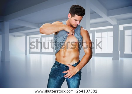 Attractive bodybuilder against white room with windows - stock photo